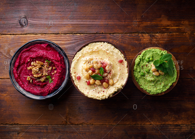 Creamy chickpea hummus, green pea hummus and spicy roasted beetroot dip with walnuts