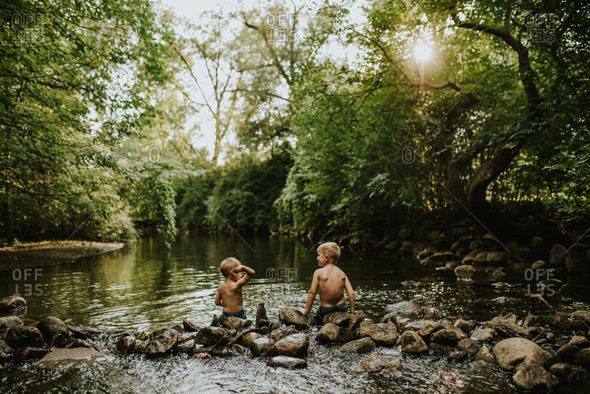 Two little boys sitting on rocks in a creek, skipping stones