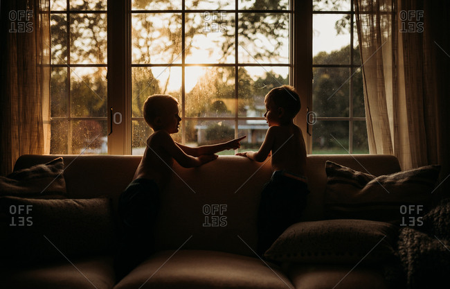 Silhouette shot of two boys looking out front window of their home and talking as the golden sunset streams through the window