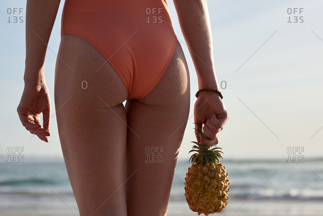 Tropical holiday travel concept, woman holding pineapple walking along the ocean beach sea carefree vacation