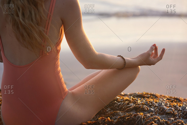 Woman meditating by the ocean at sunset, sitting on rocks facing the ocean zen peaceful