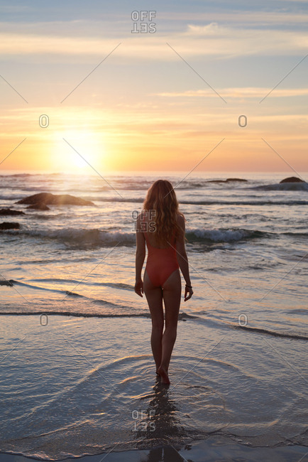 Travel wanderlust, woman walking into the ocean at sunset beautiful waves lots of copy space