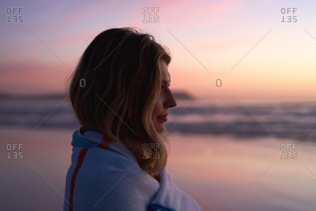 Portrait of a beautiful young woman at sunset by the ocean