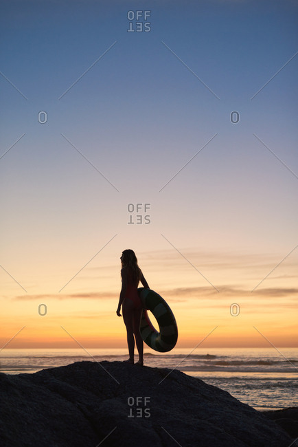 Holiday wanderlust travel summer carefree concept, woman on beach holiday holding float lots of copy space in pink orange sunset sky