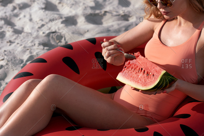 Woman eating watermelon on a pool float on sandy beach, carefree summer holiday concept