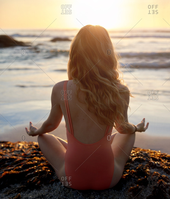 zen woman meditating at the beach, sunset receiving positive energy from the ocean