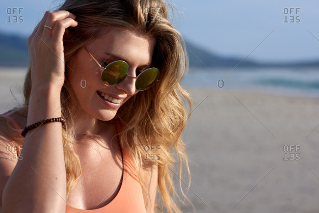 Portrait of happy smiling blonde woman at the beach, relaxed carefree holiday fun with copy space