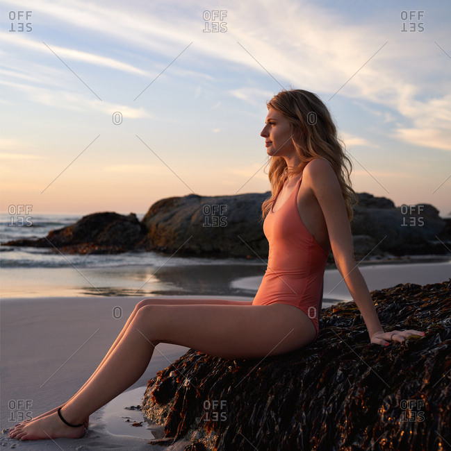Portrait of young woman watching the waves from the beach at sunset