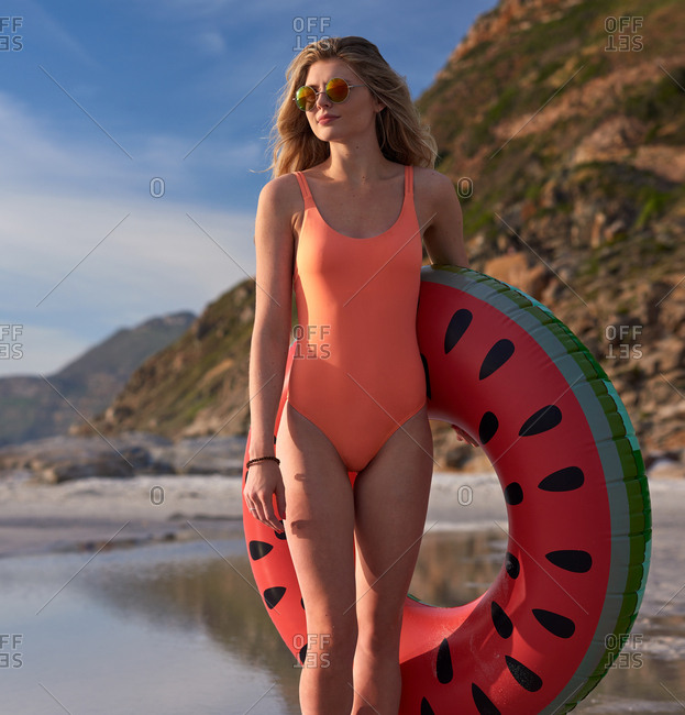 Beautiful young woman on sandy beach, taking cute watermlon float to the ocean carefree holiday summer