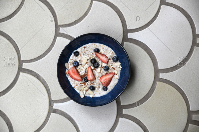 Bowl of oatmeal topped with almonds, strawberries, and blueberries