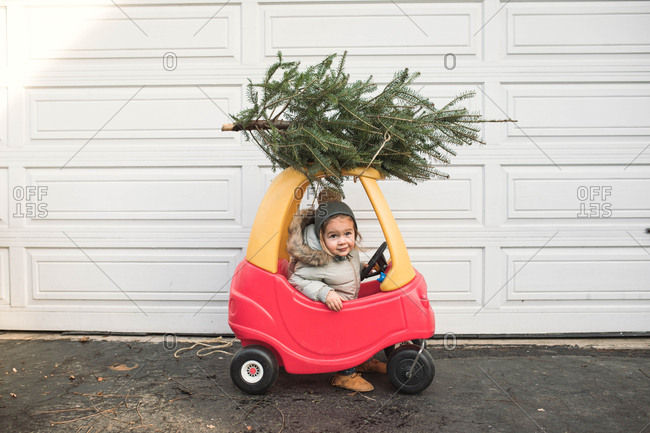 Little girl in a toy car with a Christmas tree tied to the top