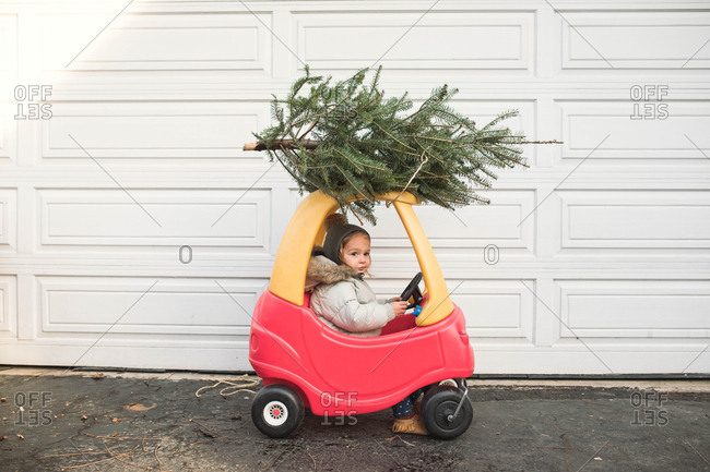 Child playing with toy car with a Christmas tree strapped to the top