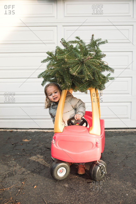 Girl driving a toy car with a Christmas tree strapped to the top