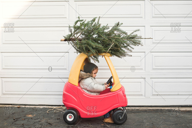 Side view of a child driving a toy car with a small Christmas tree strapped to the top