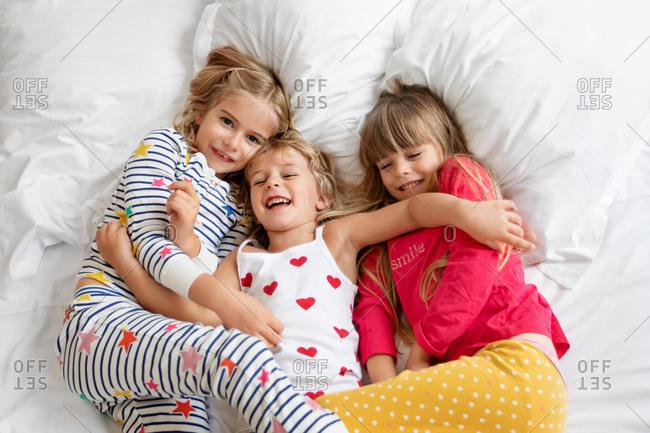 Three smiling girls wearing pajamas lying together on bed