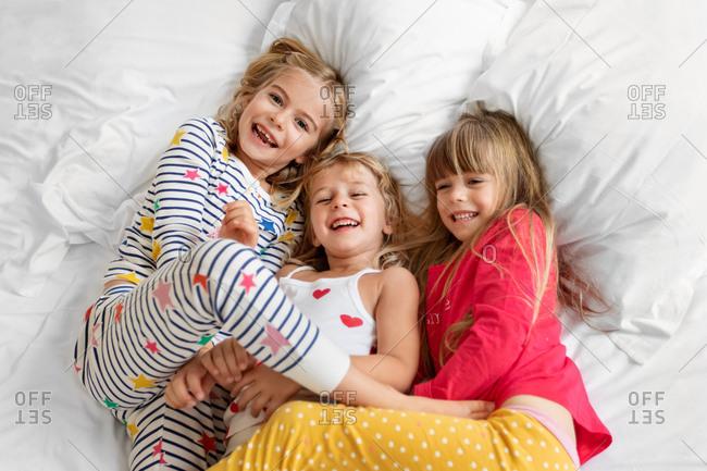 Three laughing girls wearing pajamas lying together on bed