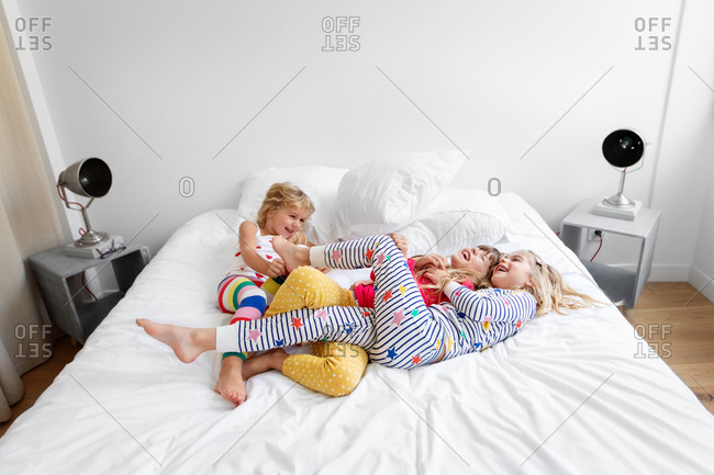 Laughing girls wearing pajamas tickling each other on bed