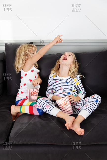 Girl feeding popcorn to her friend