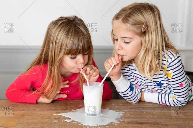 Two girls drinking a glass of milk together