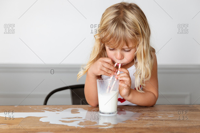 Girl blowing bubbles in a glass of milk on a messy table