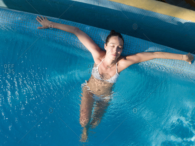 Woman enjoying bath in swimming pool- eyes closed