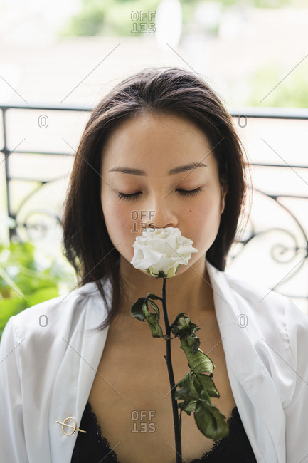 Portrait of attractive young woman smelling at white rose