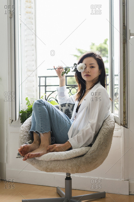 Portrait of attractive young woman sitting at the window with white rose