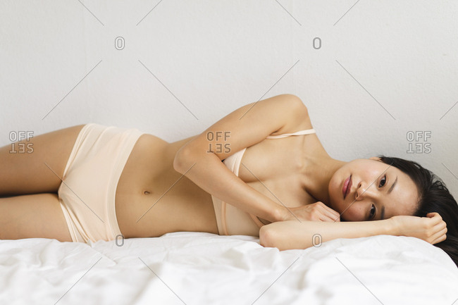 Portrait of attractive young woman in lingerie lying in bed