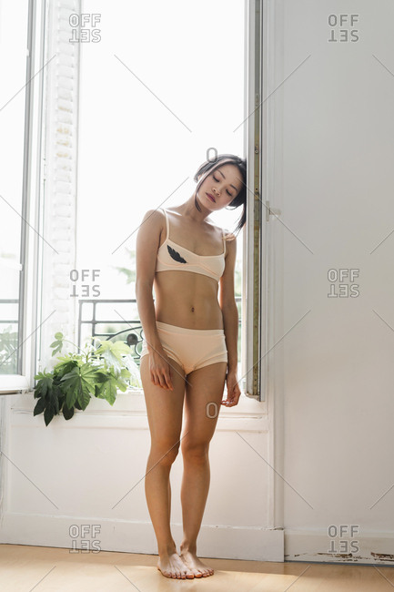 Attractive young woman in lingerie standing at the window