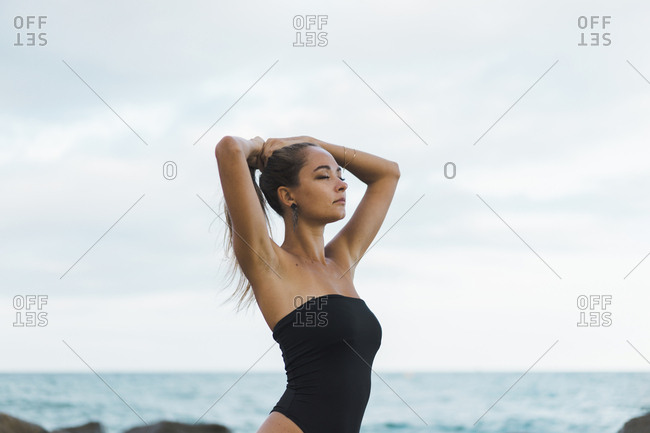 Beautiful young woman with closed eyes wearing swimsuit at the seafront