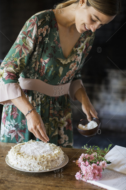 Smiling young woman garnishing home-baked cake