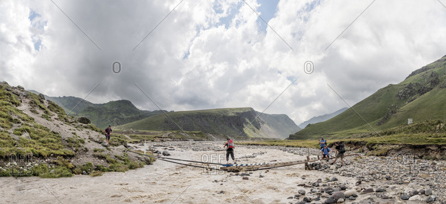 Russia- Caucasus- Mountaineers crossing river in Upper Baksan Valley