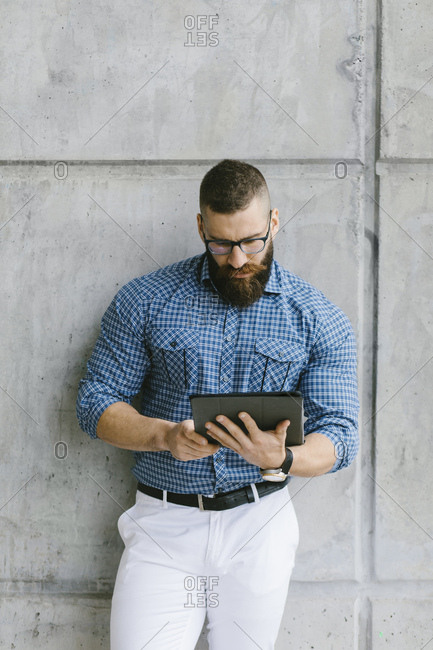 Bearded hipster businessman wearing glasses and plaid shirt leaning against wall using tablet