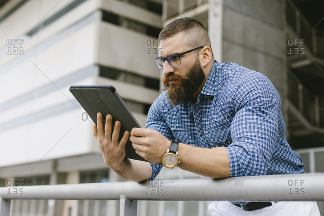 Bearded hipster businessman wearing glasses- wrist watch and plaid shirt using digital tablet