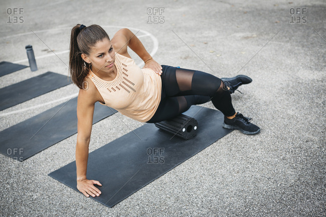 Young woman doing side plank exercise with fascia roll outdoors