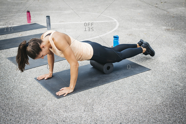 Young woman doing workout exercise with fascia roll outdoors