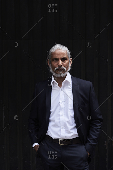 Portrait of stylish senior businessman with grey hair and beard standing against dark background