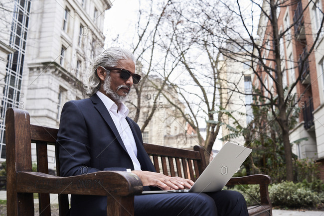 UK- London- senior businessman sitting on bench outdoors working on laptop