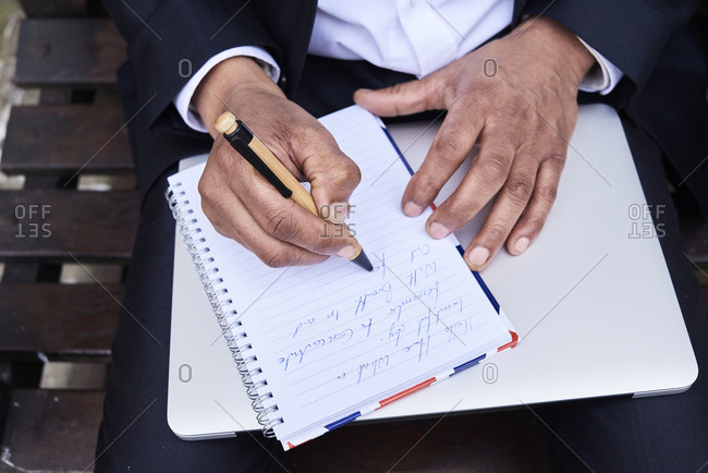 Businessman writing notes in notebook- close-up