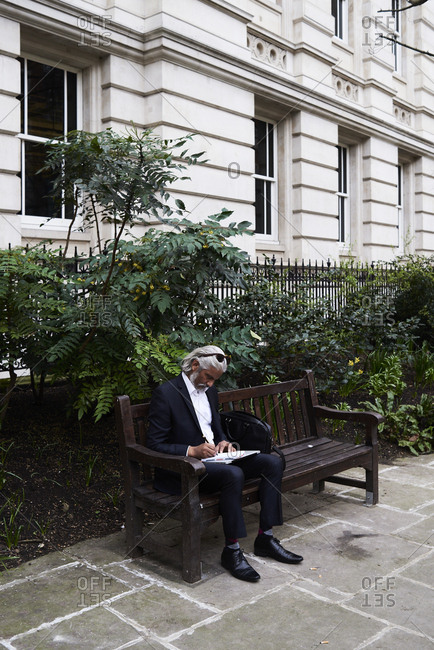 Senior businessman sitting on bench outdoors writing notes in notebook
