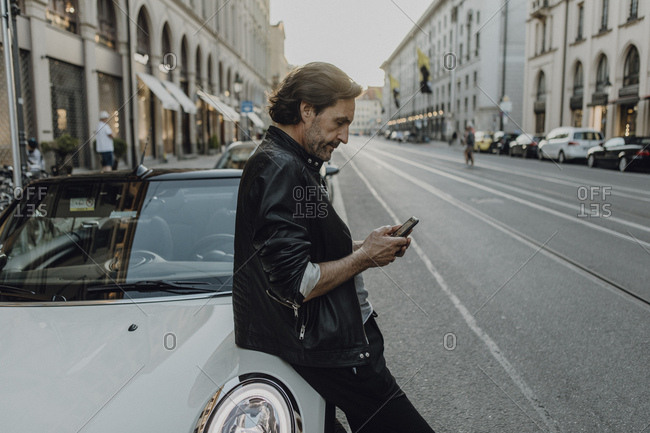 Mature man leaning on car- holding smartphone- Munich- Bavaria- Germany