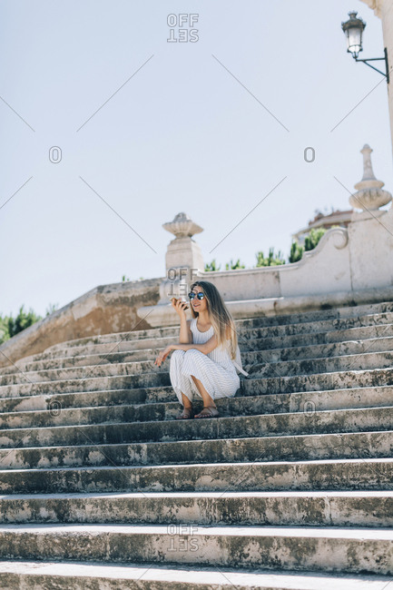 Spain- Valencia- woman sitting on stairs using smartphone