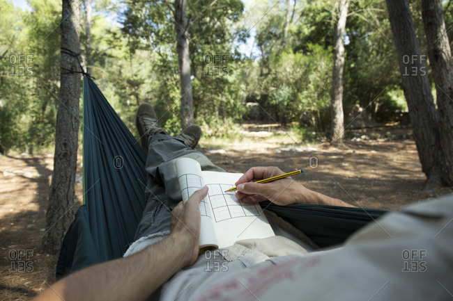 Man lying in hammock in the woods relaxing with puzzle book- partial view