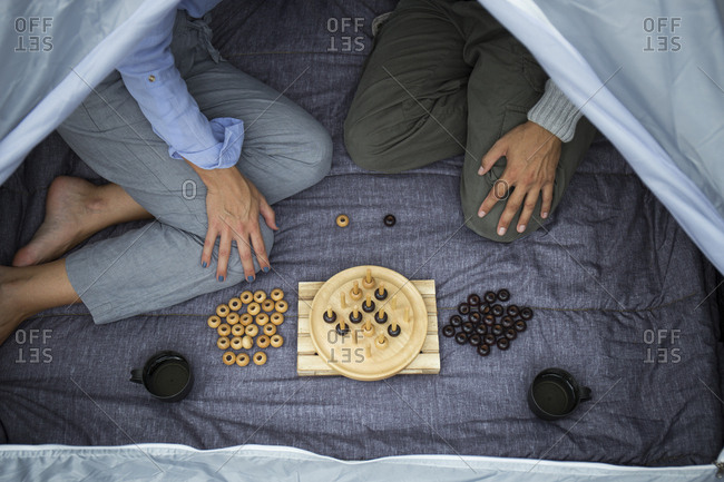 Couple sitting in tent playing board game- partial view