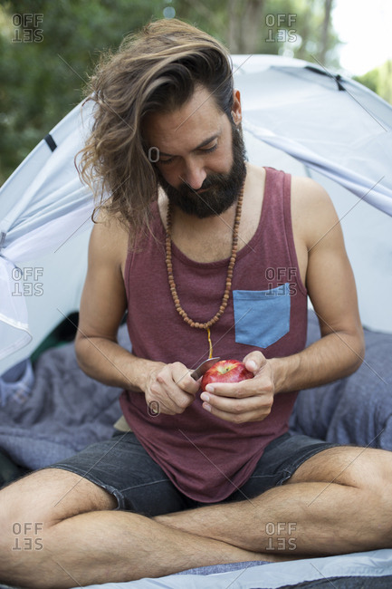 Man sitting in front of a tent peeling an apple