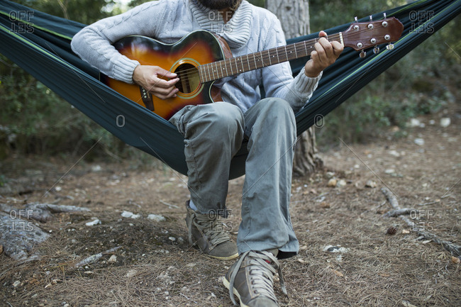 Man sitting in hammock playing guitar in the woods- partial view
