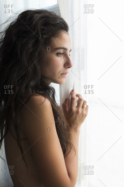 Young naked woman looking through window