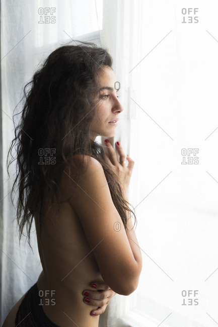 Young shirtless woman standing at the window watching something