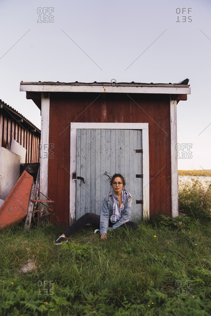 Portrait of a young woman sitting in grass in front of a wooden shack