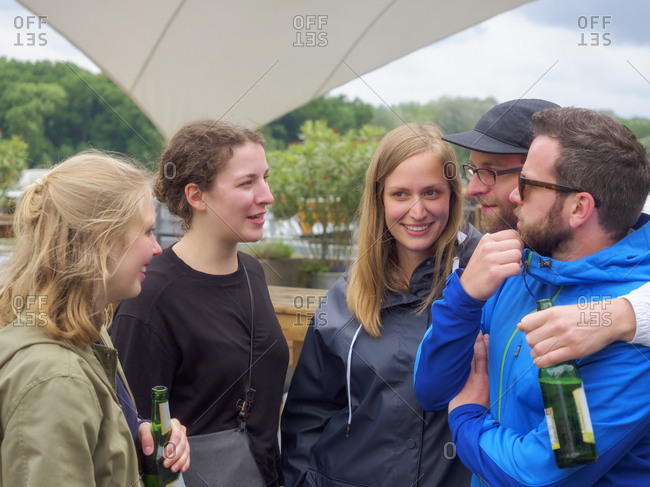 Friends with beer bottles socializing outdoors